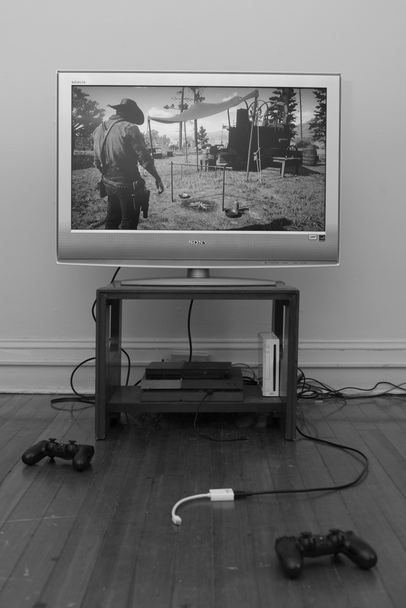 PS4 controllers sit scattered on the floor. The TV shows a cowboy standing in front of a rural camp.