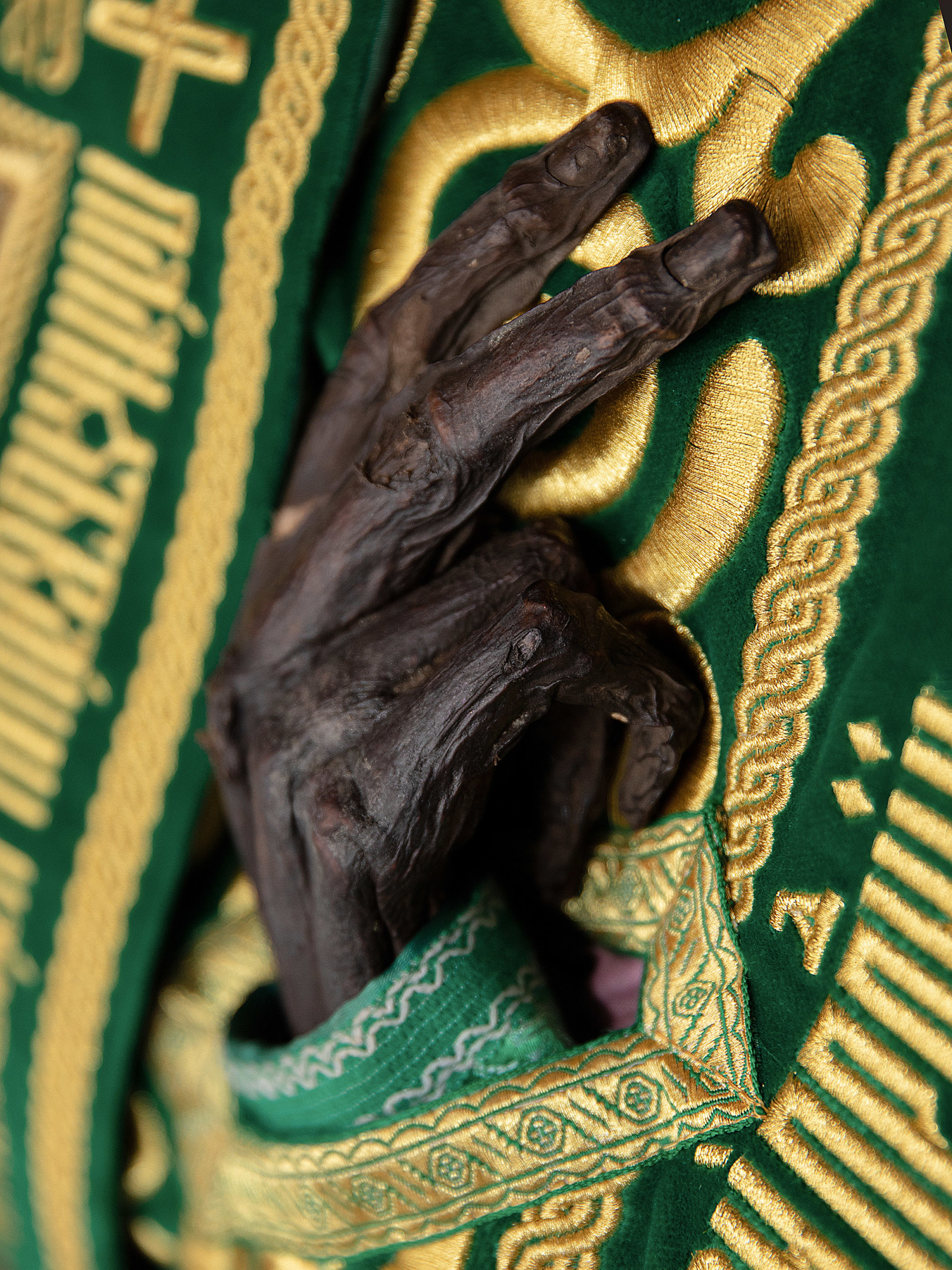 The black, dessicated hand of a saint, dressed in finery.