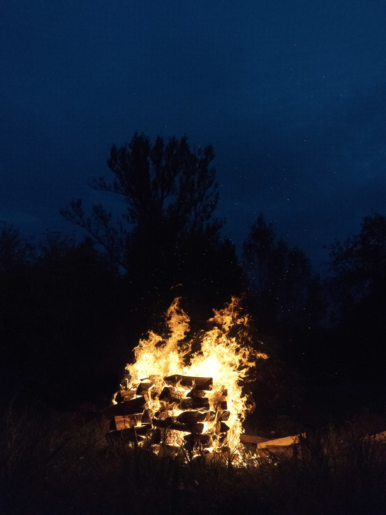 A log pyre burns in the dead of night.