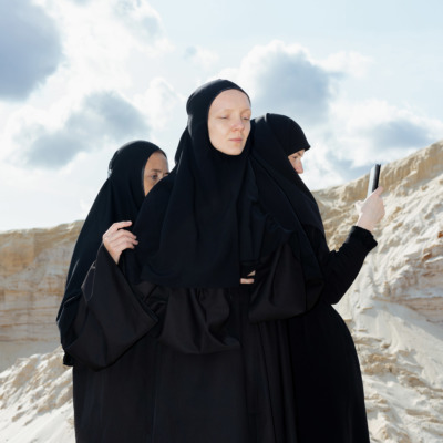 Three religious women stand in a desert, one with a cameraphone.