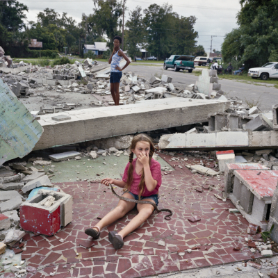 A young girl holding a snake sits in the ruins of a demolished home. Nobody seems concerned by the scene.